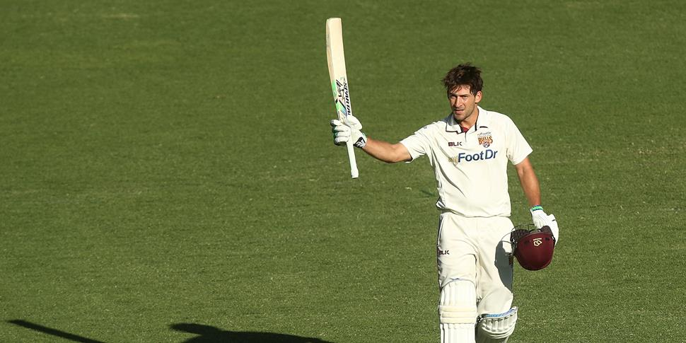 joe burns raises his bat after century.jpg