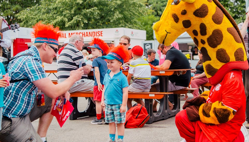 Lanky the giraffe with junior fans at the family event at Emirates Old Trafford Lancashire Cricket Club.jpg